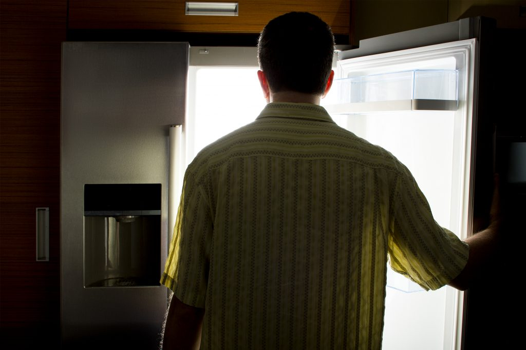Man looking for food in an open fridge in a dark kitchen late at night.  The man looks like a bachelor.  He is hungry and starving so he is looking for a snack.  The kitchen is dark like it is night time.