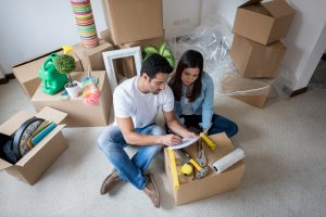 Latin couple moving house and packing in boxes while looking at checklist